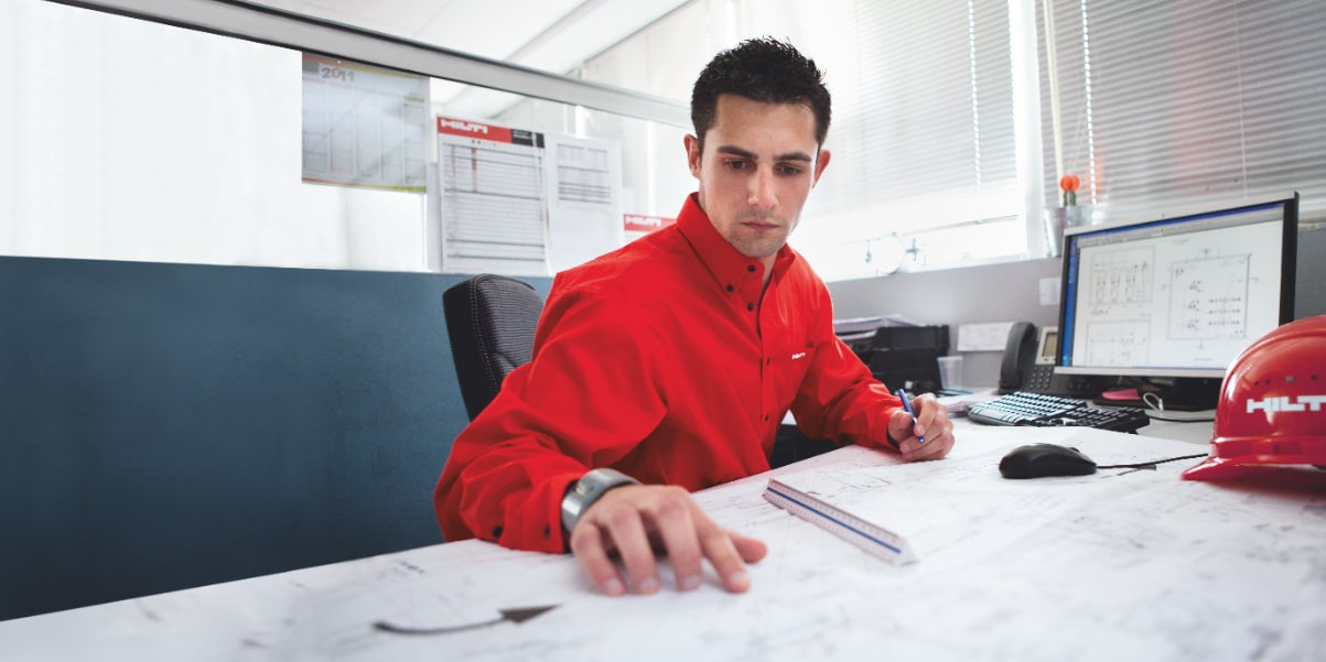 Photo of a Hilti Engineer at his desk, carrying out an engineering judgement for a customer.